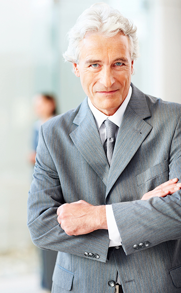 Photo of a mature business man smiling with hands folded