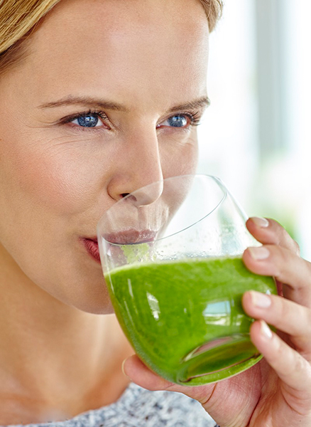 Healthy woman drinking green vegetables