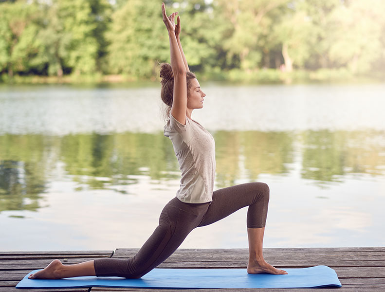 Active slender young woman exercising outdoors on a wooden deck overlooking a tranquil lake doing yoga poses in a side view